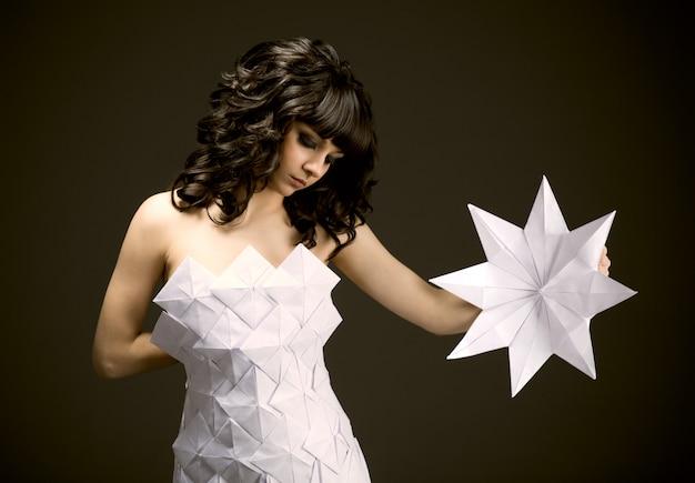 Triest jonge brunette meisje in origami jurk
