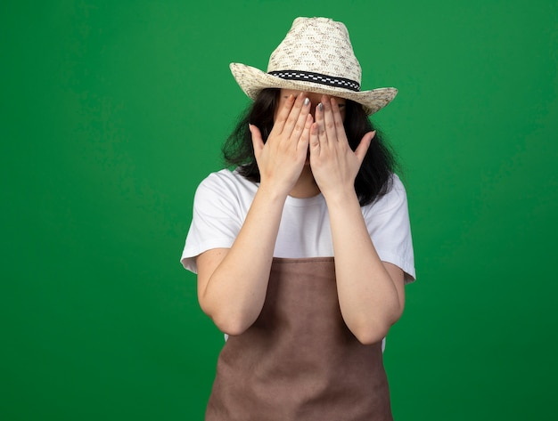 Triest jonge brunette vrouwelijke tuinman in optische bril en uniform dragen tuinieren hoed legt handen op gezicht geïsoleerd op groene muur