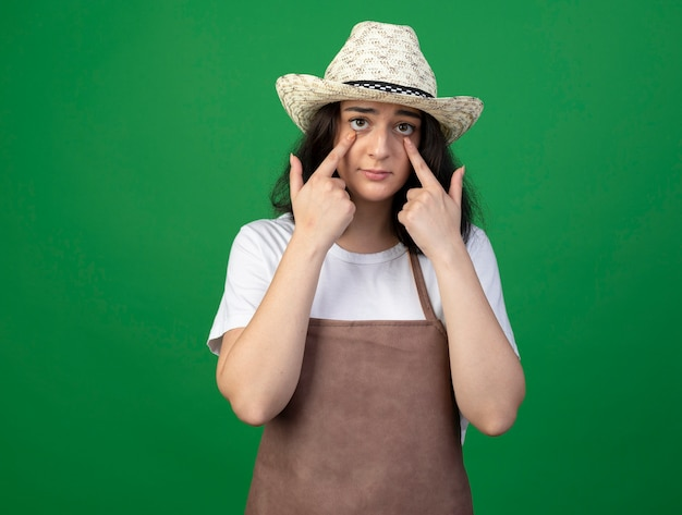 Triest jonge brunette vrouwelijke tuinman in optische bril en uniform dragen tuinieren hoed trekt oogleden geïsoleerd op groene muur