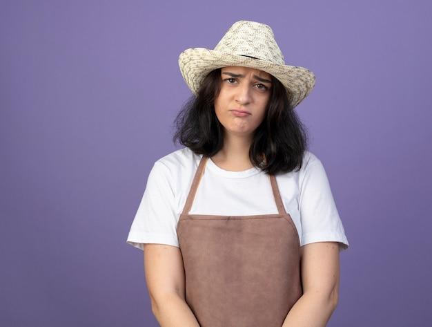 Triest jonge brunette vrouwelijke tuinman in uniform dragen tuinieren hoed kijkt naar voorzijde geïsoleerd op paarse muur