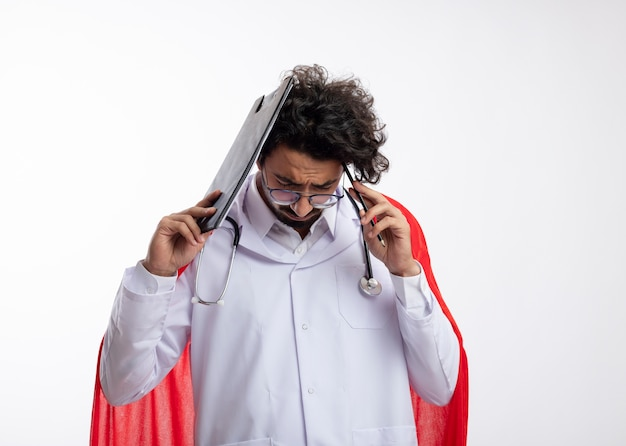 Triest jonge kaukasische superheld man in optische bril, het dragen van doktersuniform met rode mantel en met een stethoscoop om de nek houdt klembord en potlood aan het hoofd met kopie ruimte