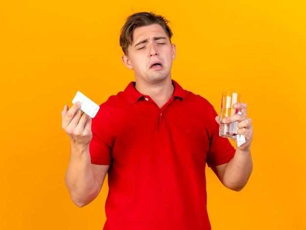 Triest jonge knappe blonde zieke man met pack van medische tabletten glas water en servet huilen met gesloten ogen geïsoleerd op een oranje achtergrond