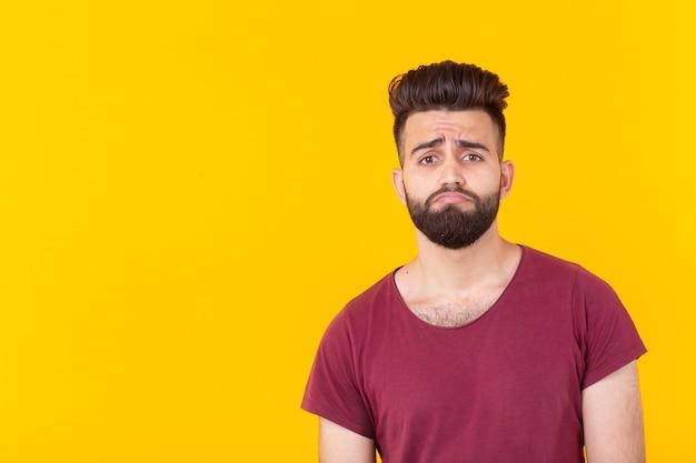 Triest jonge knappe man hipster met een baard in een bordeauxrood t-shirt poseren op een gele ondergrond. concept van frustratie. advertentie ruimte