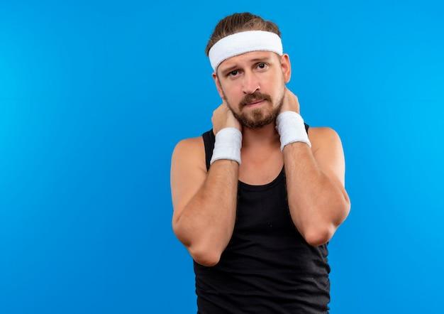Triest jonge knappe sportieve man met hoofdband en polsbandjes handen op nek geïsoleerd op blauwe ruimte