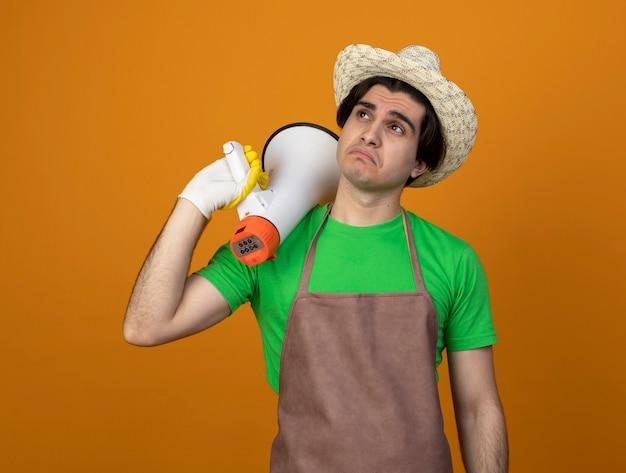 Triest jonge mannelijke tuinman in uniform dragen tuinieren hoed met handschoenen kijken kant houden luidspreker op schouder geïsoleerd op oranje