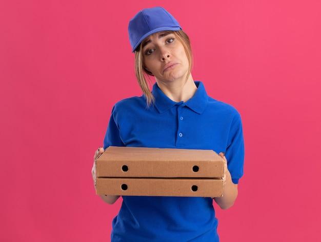 Triest jonge mooie levering meisje in uniform houdt pizzadozen op roze