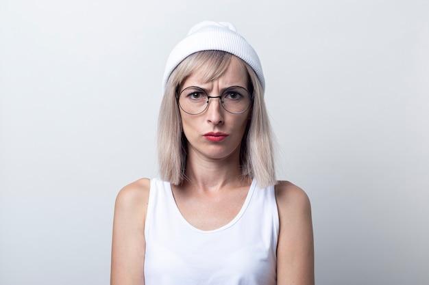 Triest jonge vrouw in glazen, een witte hoed op een lichte achtergrond.