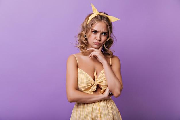 Triest jonge vrouw met geel lint in haar poseren op paars. indoor portret van peinzende krullende dame in zomer outfit.