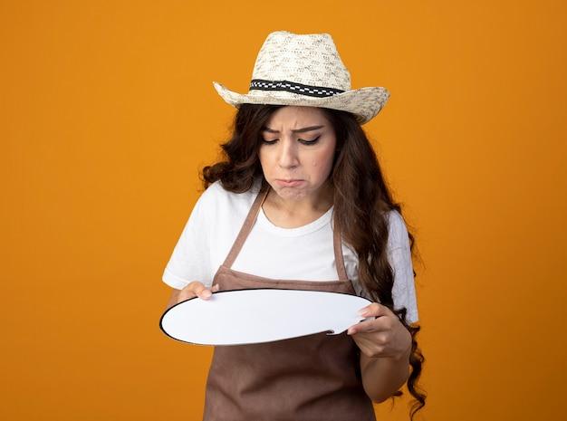 Triest jonge vrouwelijke tuinman in uniform dragen tuinieren hoed houdt en kijkt naar tekstballon geïsoleerd op oranje muur