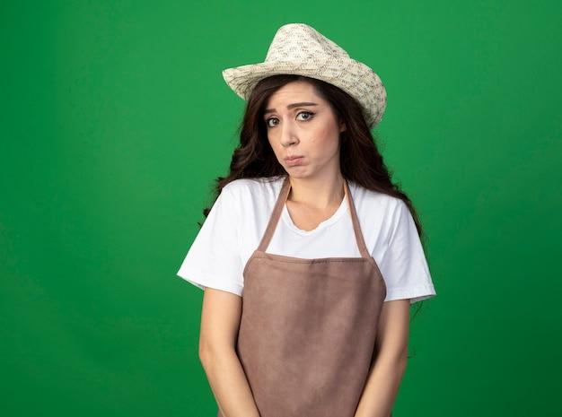 Triest jonge vrouwelijke tuinman in uniform dragen tuinieren hoed kijkt naar voorzijde geïsoleerd op groene muur