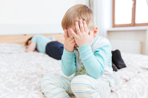 Triest jongetje zittend en huilend op bed terwijl zijn vader slaapt