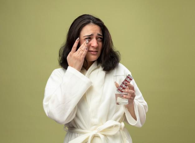 Triest kaukasisch ziek meisje dragen gewaad houden glas water en pak medische pillen kijken kant afvegende oor geïsoleerd op olijfgroene achtergrond met kopie ruimte