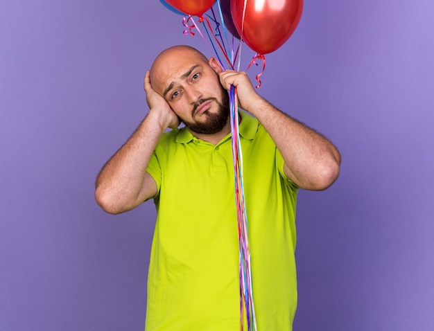 Triest kijken naar camera jonge man met ballonnen greep hoofd