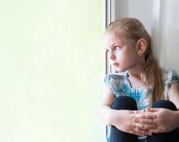 Triest kind meisje bij het raam
