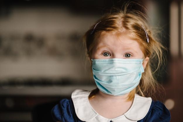 Triest kind meisje met een medisch masker op het gezicht. blijf thuis. isolatie. quarantaine. waarschuwing voor de gevaren en veiligheidsmaatregelen tegen coronavirus. close-up portret. covid-19, symptomen van epidemische virussen.