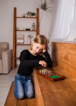 Triest klein blond meisje zit en speelt schaak in de kamer