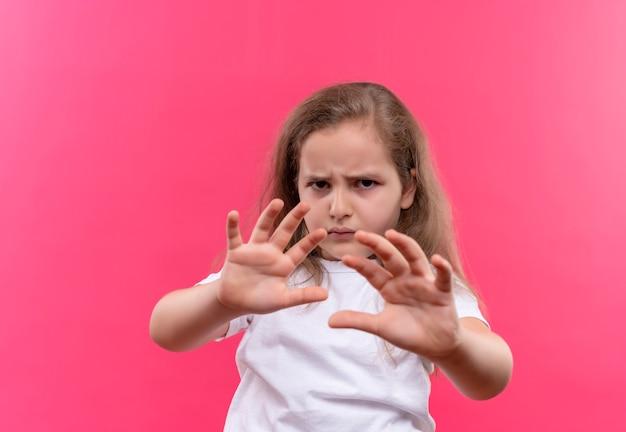 Triest klein schoolmeisje dat een wit t-shirt draagt dat stopgebaar op geïsoleerde roze achtergrond toont
