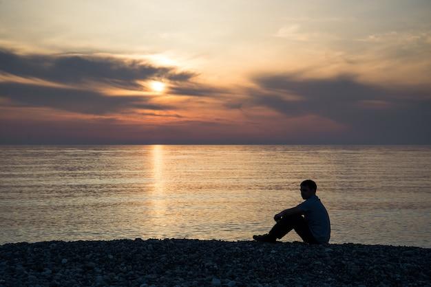 Triest man silhouet bezorgd op het strand bij zonsondergang met de zon