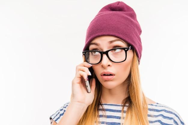 Triest meisje in hoed en bril praten over de telefoon