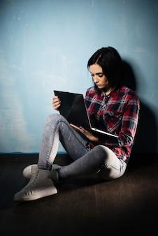 Triest meisje lijdt aan afhankelijkheid van sociale netwerken zittend op de vloer met een notebook