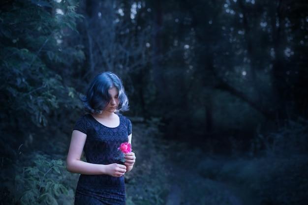 Triest meisje met blauw haar en roze roos in nacht bos