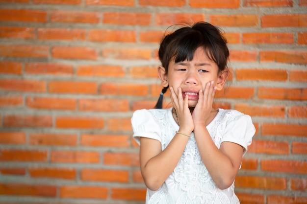 Triest meisje portret, aziatische kleine meisjes verdrietig beledigd meisje huilt.