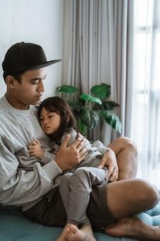 Triest meisje rustend op de borst van haar vader