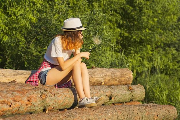 Triest meisje zit in de natuur met een pluizige paardebloem, ernstige ongelukkige tiener