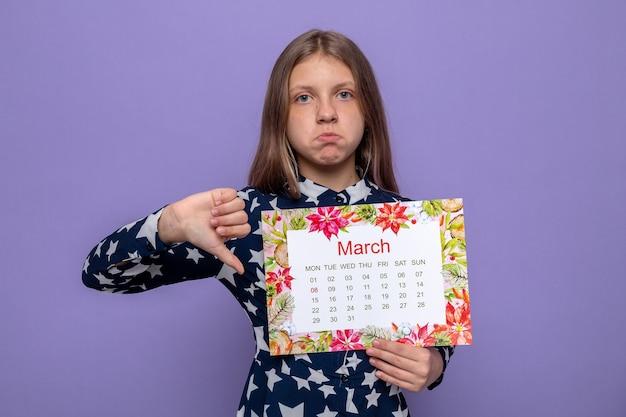 Triest met duim omlaag mooi klein meisje op gelukkige vrouwendag met kalender