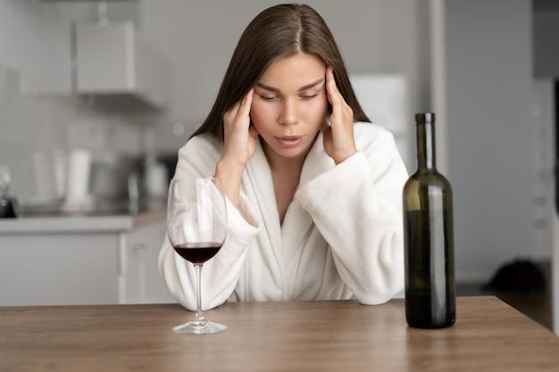 Triest moe vrouw drinken van wijn thuis