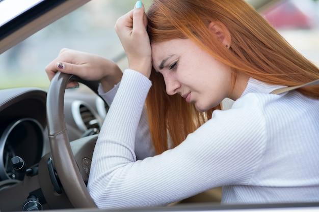 Triest moe yound vrouw bestuurder zitten achter het stuur van de auto in de file.