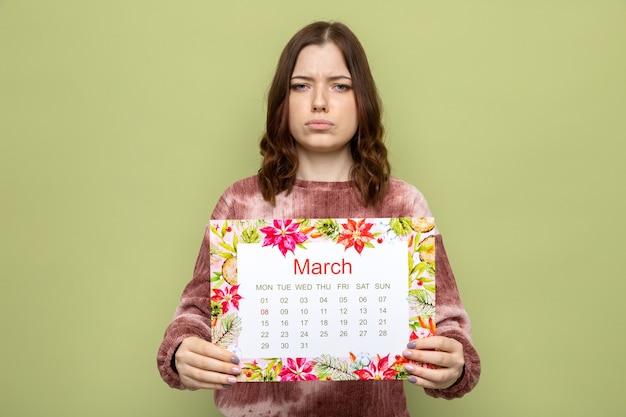 Triest mooi jong meisje op gelukkige vrouwendag die kalender uithoudt