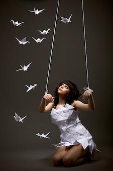 Triest mooie jonge blanke meisje in origami