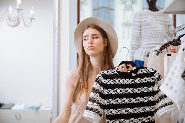 Triest mooie jonge vrouw in hoed winkelen in kledingwinkel