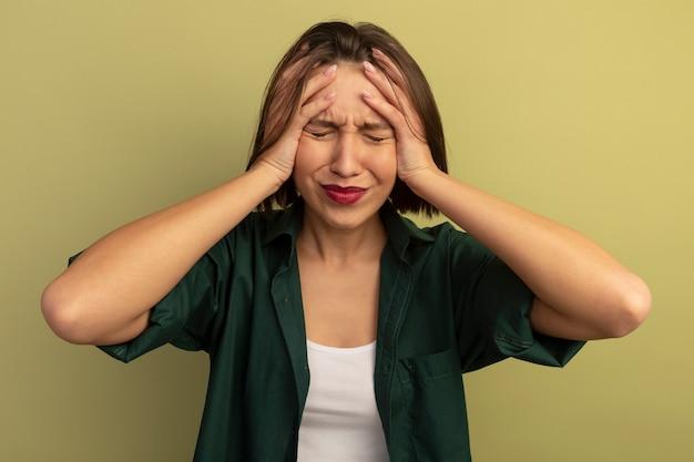 Triest mooie vrouw houdt hoofd geïsoleerd op olijfgroene muur