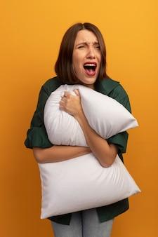 Triest mooie vrouw houdt kussen en schreeuwt naar kant geïsoleerd op oranje muur