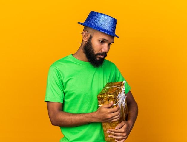 Triest naar beneden kijkende jonge afro-amerikaanse man met een feesthoed met een geschenkdoos geïsoleerd op een oranje muur