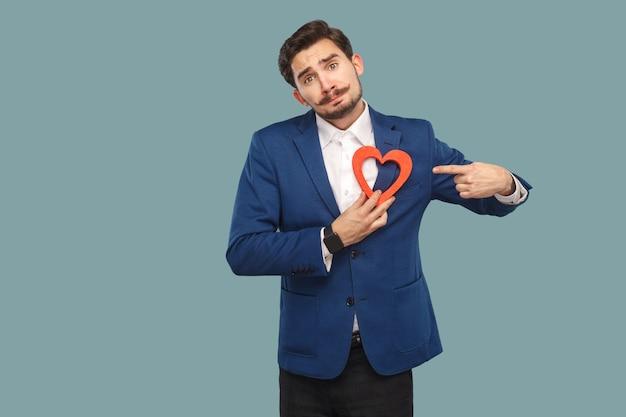 Triest ongelukkig gebroken hart man in blauwe jas en wit overhemd, permanent en rood hart vorm te houden en camera kijken en wijzende vinger. binnen, studio-opname geïsoleerd op lichtblauwe achtergrond