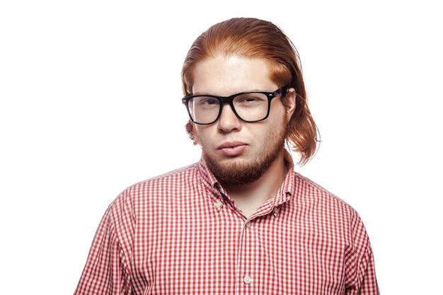 Triest ongelukkige bebaarde leeskop zakenman met rood shirt en sproeten camera kijken