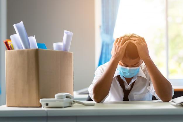 Triest ontslagen aziatische zakenman buiten zitten na te zijn afgewezen concept van bedrijfsfalen en werkloosheidsprobleem als gevolg van de wereldwijde impact van covid-19.