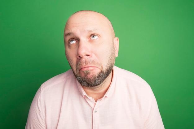 Triest opzoeken van middelbare leeftijd kale man met roze t-shirt geïsoleerd op groen