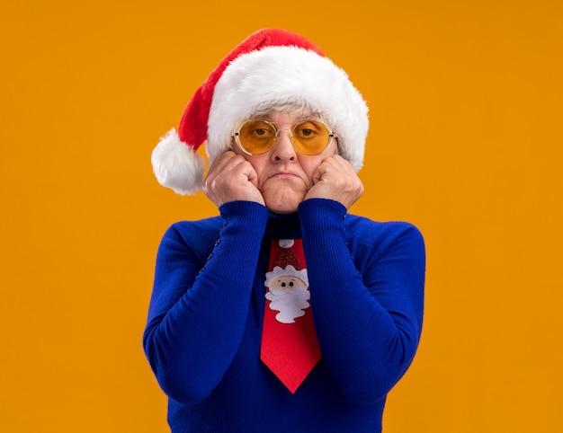 Triest oudere vrouw in zonnebril met kerstmuts en santa stropdas zet handen op gezicht geïsoleerd op oranje muur met kopieerruimte