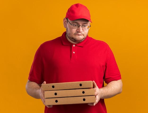 Triest overgewicht jonge bezorger in optische bril met pizzadozen naar beneden kijken geïsoleerd op oranje muur met kopieerruimte