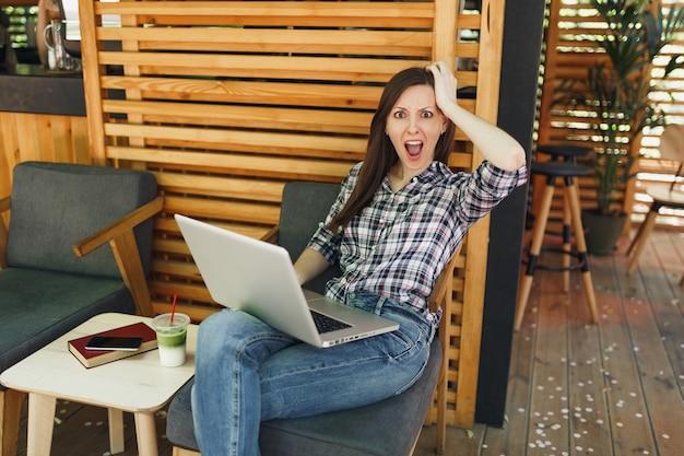 Triest overstuur schreeuwende vrouw in openlucht straat zomer coffeeshop zittend in vrijetijdskleding, werken op moderne laptop pc-computer tijdens vrije tijd