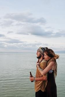 Triest paar dat zeegezicht bekijkt