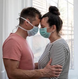 Triest paar in maskers poseren in de buurt van venster thuis