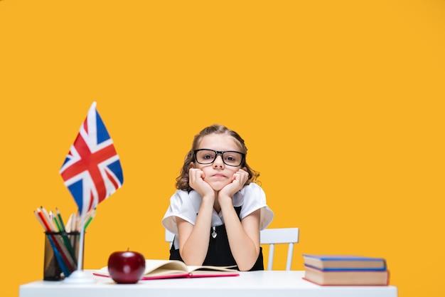 Triest saai kaukasisch schoolmeisje in glazen die thuis engelse les studeert, vlag van groot-brittannië