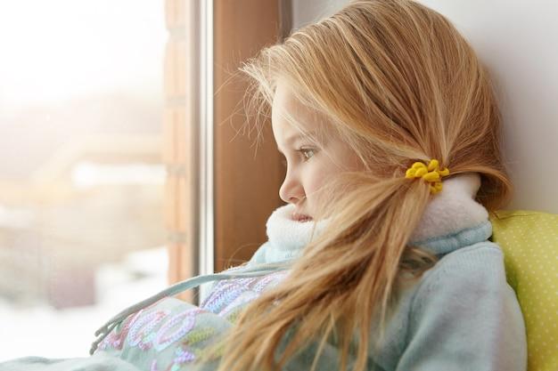 Triest schattig vrouwelijk kind met blonde haren, zittend op de vensterbank