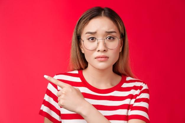 Triest schattige aziatische vrouwelijke collega moe werkkleding bril fronsend wijzend naar links kijken camera boos d...