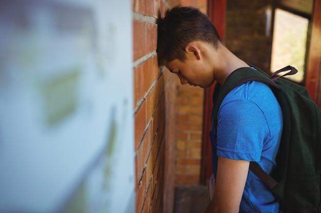 Triest schooljongen leunend op bakstenen muur